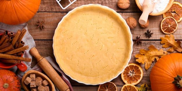 Pompoen en voedselingrediënten, kruiden, kaneel en keukengerei op oude rustieke houten achtergrond. concept zelfgemaakte bakken voor vakantie. pompoentaart en koekjes koken voor thanksgiving day. banier.
