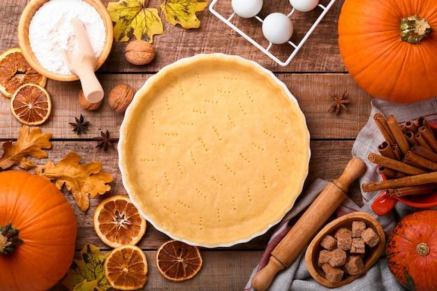 Pompoen en voedselingrediënten, kruiden, kaneel en keukengerei op oude rustieke houten achtergrond. concept zelfgemaakte bakken voor vakantie. pompoentaart en koekjes koken voor thanksgiving day.