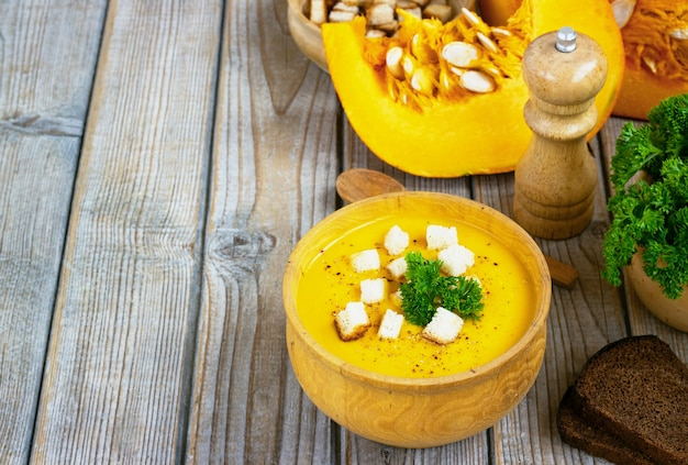 Pompoen- en wortelsoep, tadka met room en peterselie op donkere houten tafel. bovenaanzicht.