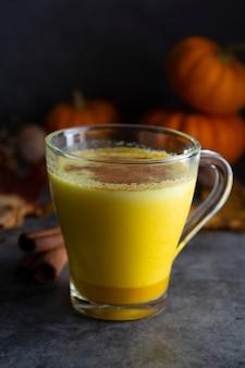 Pompoen gekruide latte macchiato op een donker hout