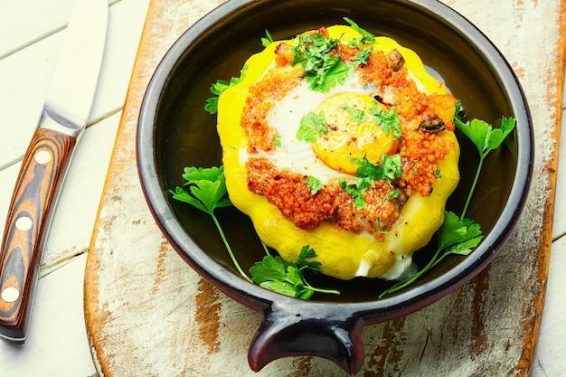 Pompoen gevuld met couscous en champignons. gebakken patisson met shakshuka.