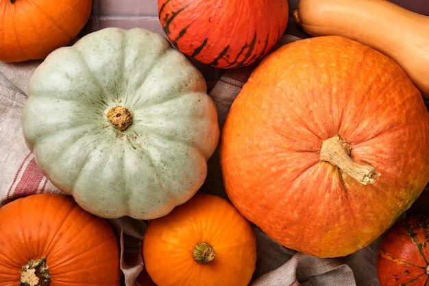 Pompoen. herfst voedsel achtergrond met kaneel, noten en seizoensgebonden kruiden op oude keramische tegels achtergrond. pompoen of appeltaart en koekjes koken voor thanksgiving en herfstvakantie. bovenaanzicht.