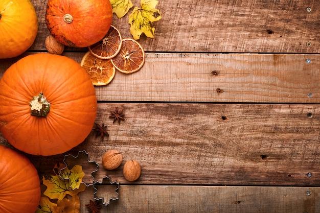 Pompoen. herfst voedsel achtergrond met kaneel, noten en seizoensgebonden kruiden op rustieke achtergrond. pompoen of appeltaart en koekjes koken voor thanksgiving en herfstvakantie. bovenaanzicht met kopie ruimte.