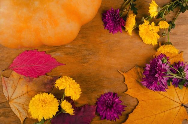 Pompoen, herfstbloemen en bladeren