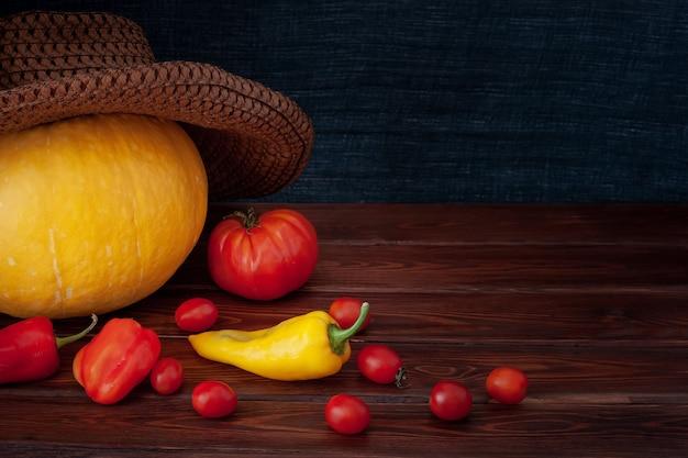 Pompoen in een hoed, verspreide rode tomaten en paprika's, een gele paprika. tomaten zijn klein en één groot. borden zijn bruin, een achtergrond van een sjaalstof. geschikt voor halloween. vignet.