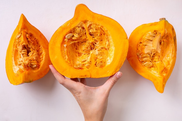 Pompoen in stukken gesneden op een lichte achtergrond. herfst voedsel concept. oogst in de handen.