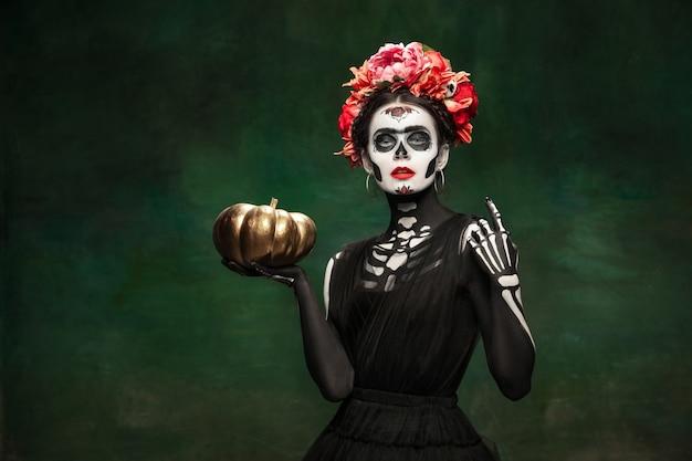 Pompoen. jong meisje zoals santa muerte saint dood of suikerschedel met lichte make-up. portret geïsoleerd op donkere groene studio achtergrond met copyspace. het vieren van halloween of dag van de doden.