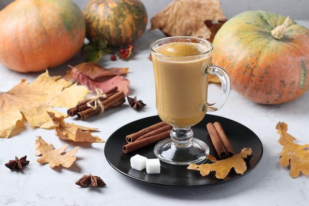 Pompoen latte met kruiden in een glasglas op grijze achtergrond met pompoenen en herfstbladeren, close-up. horizontaal formaat.