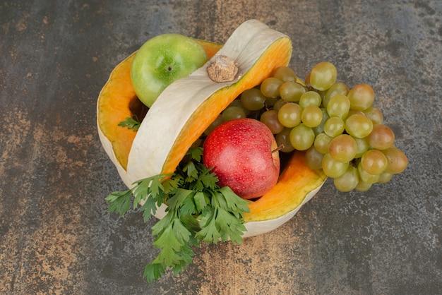 Pompoen met appels en druiven op marmeren oppervlak.
