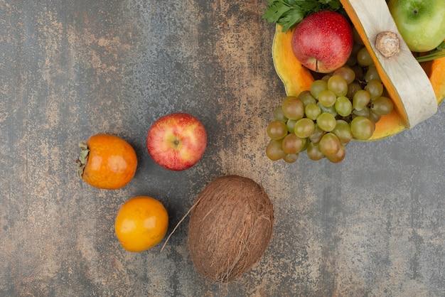Pompoen met appels, kokos en druiven op marmeren muur