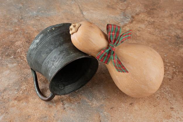 Pompoen met boog en oude ketel op marmer.