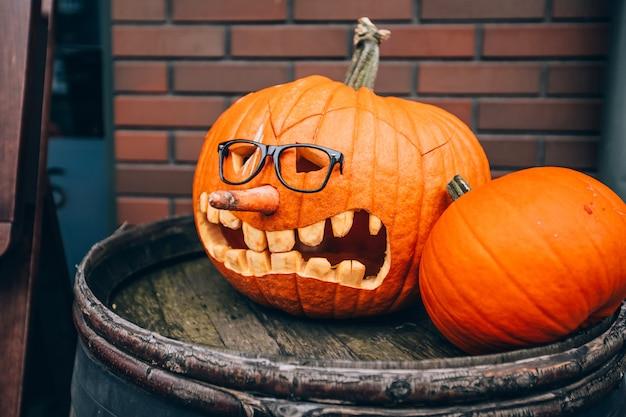 Pompoen met een gezicht staat op straat en versiert de straat die voorbijgangers bang maakt. pompoen met een gebeeldhouwd gezicht in de schemering. sinistere sfeer. fijne halloween.