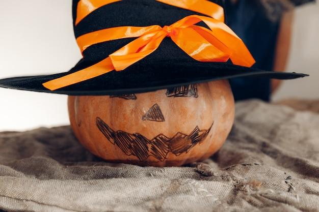 Pompoen met geschilderd gezicht en heksenhoed. halloween-concept.