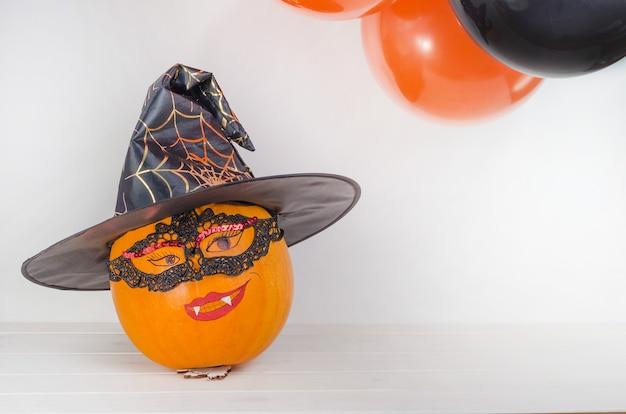 Pompoen met geschilderd gezicht in heksenhoed in de buurt van oranje en zwarte ballonnen