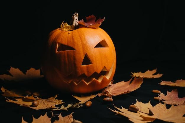 Pompoen met gesneden gezicht met oranje herfstesdoornbladeren en eikels