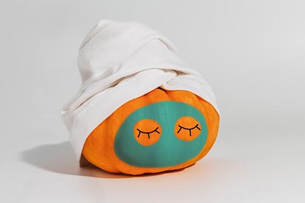 Pompoen met gezichtsmasker en handdoek geïsoleerd op een witte achtergrond. ruimte voor tekst mockup spa en halloween concept