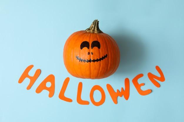 Pompoen met glimlach en tekst halloween op blauwe achtergrond