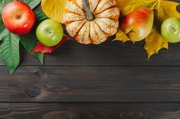 Pompoen met kleurrijke esdoornbladeren, rijpe appels en peer op donkere houten achtergrond