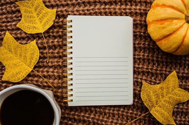 Pompoen, notebook, kopje koffie en bladeren op bruin