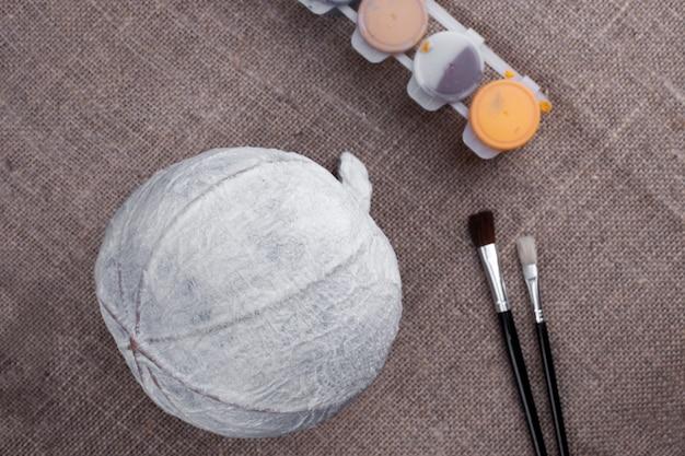 Pompoen van papier-maché, servetten op jute naast penselen en verf, het proces van het maken van een decor voor halloween.