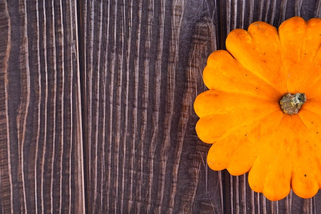 Pompoen, vers, geel, middelgroot, op een houten oppervlak. kopieer ruimte.