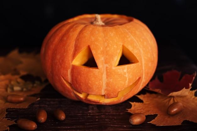 Pompoen voor halloween met herfst oranje esdoorn bladeren en eikels
