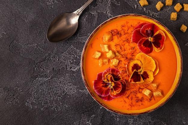 Pompoen / wortelsoep met saffraan en eetbaar bloemenviooltje