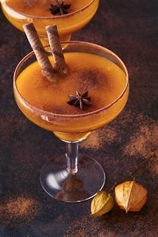 Pompoencocktail met kaneel, sinaasappelsap en cacao in glazen mokken. pompoen herfstdrankje voor halloween of thanksgiving.