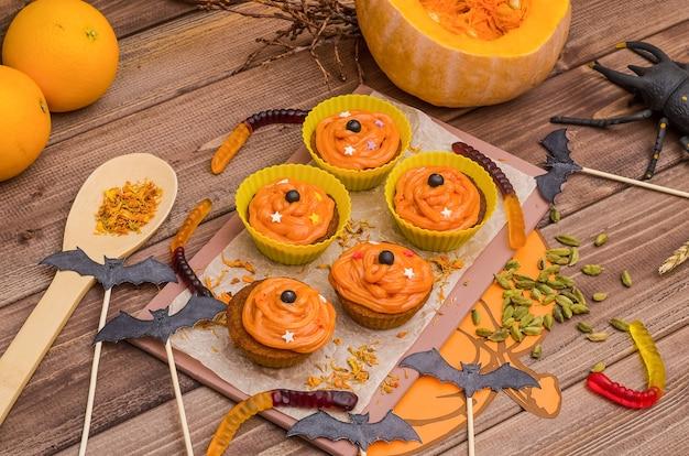 Pompoencupcakes met sinaasappelroom voor halloween. ideeën voor bakken, snoep.