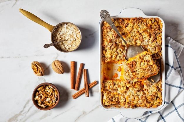Pompoendumpcake met traditionele pompoentaartkruiden: kaneel, kruidnagel, nootmuskaat met walnoten en gerolde haver bovenop geserveerd op een ovenschaal met ingrediënten op witte marmeren achtergrond, bovenaanzicht