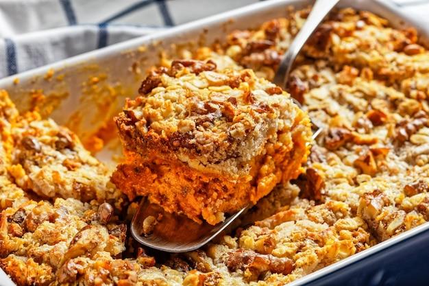 Pompoendumpcake met traditionele pompoentaartkruiden: kaneel, kruidnagel, nootmuskaat met walnoten en gerolde haver bovenop geserveerd op een ovenschaal op witte marmeren achtergrond, bovenaanzicht, close-up