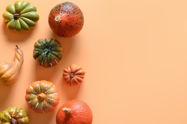Pompoenen als grens op oranje achtergrond met exemplaarruimte. thanksgiving day of halloween-sjabloon.