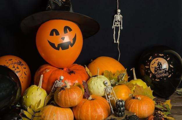 Pompoenen en ballonnen met herfstbladeren en halloween-decoratie