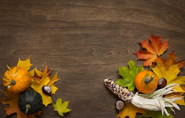 Pompoenen en esdoorn bladeren op een houten achtergrond met een kopie ruimte.