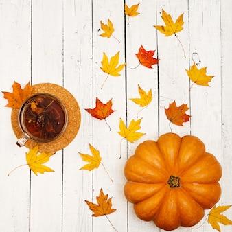 Pompoenen en gevallen bladeren op witte houten tafel