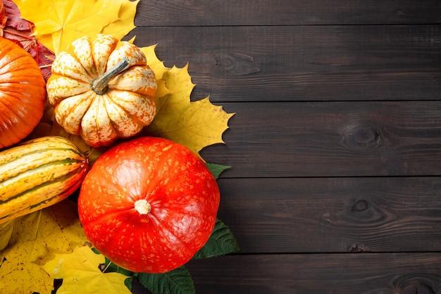 Pompoenen en herfstbladeren op donkere houten tafel