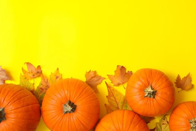 Pompoenen en herfstbladeren op gele achtergrond