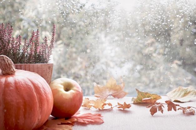 Pompoenen en herfstbladeren op het venster bord op een regenachtige dag