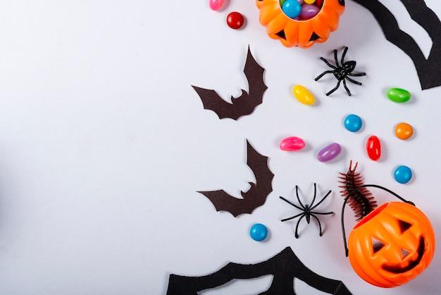 Pompoenen en snoepjes verspreid samen met vleermuizen, spinnen en duizendpoot op grijs.