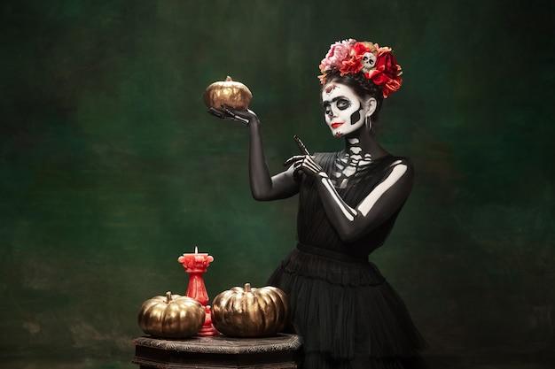 Pompoenen. jong meisje zoals santa muerte saint dood of suikerschedel met lichte make-up. portret geïsoleerd op donkere groene studio achtergrond met copyspace. het vieren van halloween of dag van de doden.