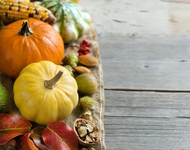 Pompoenen, maïskolf, tarwespikes, noten, eikels, bladeren en bessen op houten tafel close-up met kopie ruimte