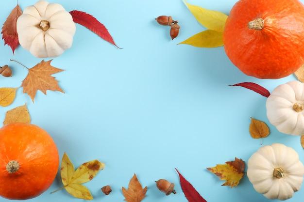 Pompoenen op een gekleurde achtergrond thanksgiving achtergrond herfst achtergrond