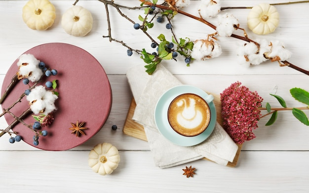 Pompoenkruid latte. blauwe koffiekop met romig schuim, gedroogde herfstbloemen, sleedoorn en kleine gele pompoenen. warme drank vallen en doos aanwezig