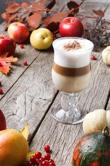 Pompoenkruid latte. glazen koffiekopje met romig schuim, gedroogde herfstbladeren, appels en kleine pompoenen op rustiek hout. herfst warme dranken, seizoensgebonden aanbod concept