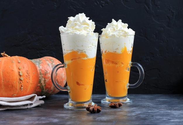 Pompoenkruid latte, smoothie, dronken cocktail met slagroom op zwart