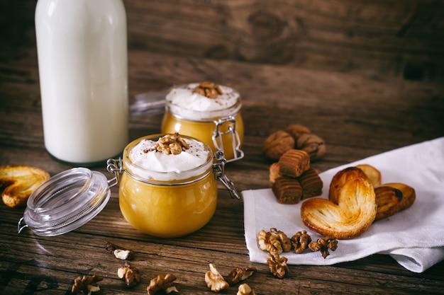 Pompoenmilkshake in glazen pot met slagroom, toffee, walnoot en honingkoekjes
