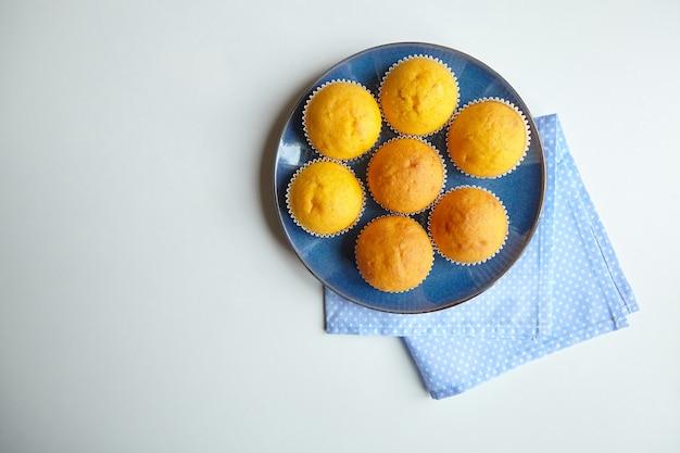 Pompoenmuffins op blauw bord op witte tafel, bovenaanzicht. zelfgemaakte bakkerij, plantaardig eten