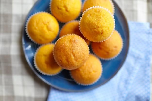 Pompoenmuffins op blauwe plaat op lijst met tafelkleed, hoogste mening. zelfgemaakte bakkerij, plantaardig voedsel