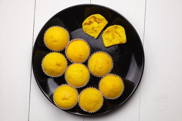 Pompoenmuffins op ronde zwarte plaat op witte lijstbovenkant