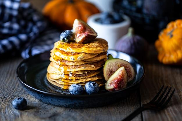 Pompoenpannenkoeken met siroop of honing, lijnzaad, vijgen, bosbessen in een donker bord op de tafel